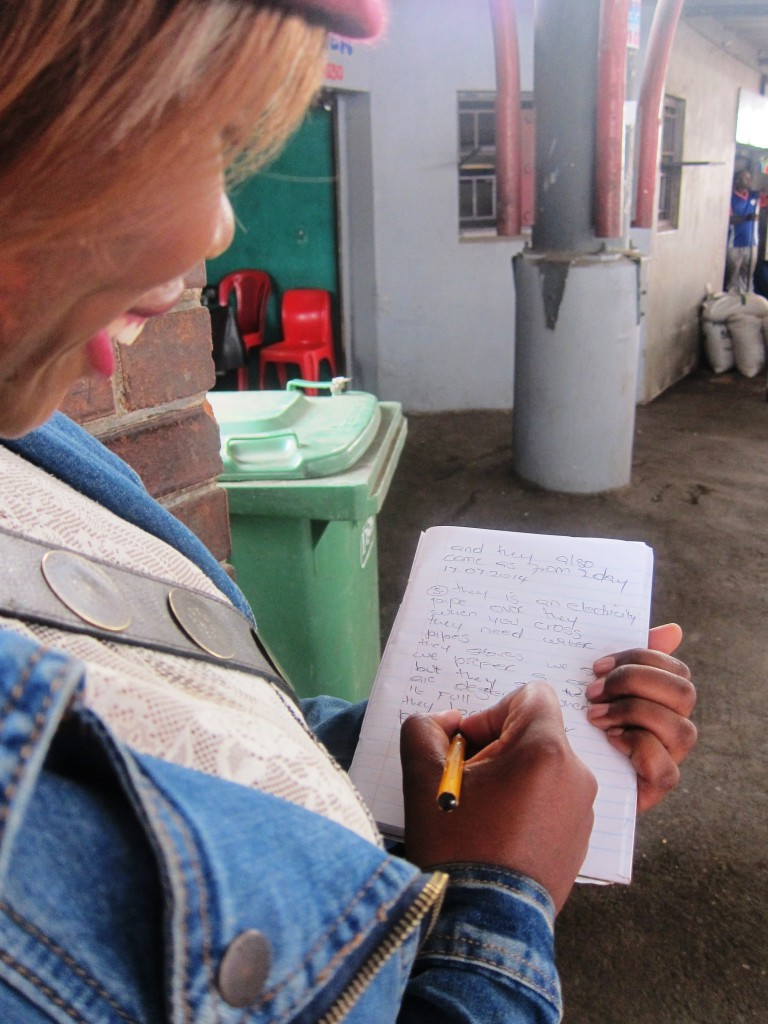 An informal trader representative taking meticulous notes from the workplace safety audit. Image: Tasmi Quazi.