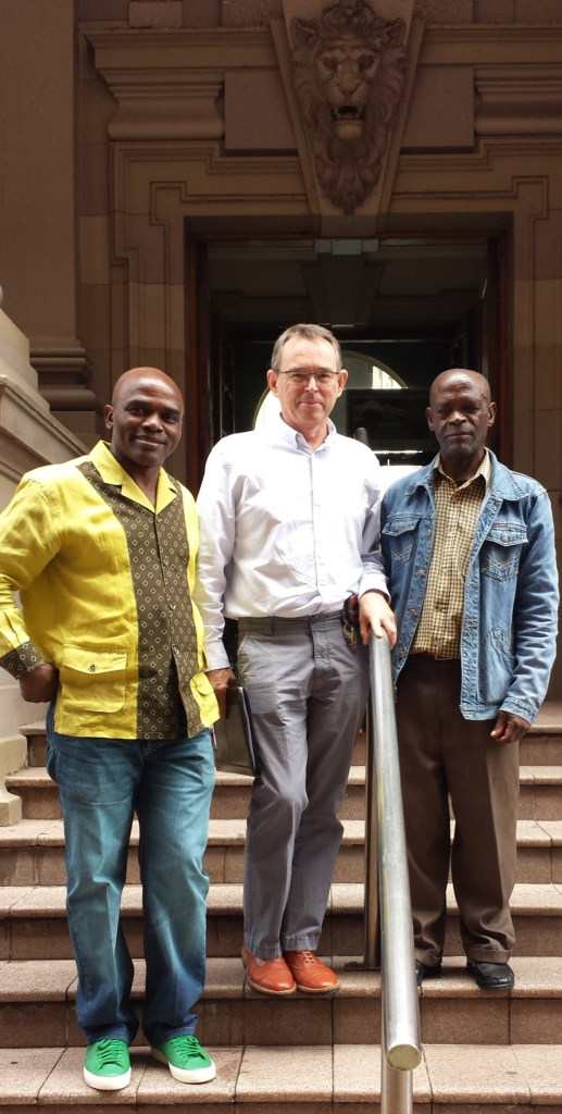 John Makwicana on the far right next to AeT Co-founders, Richard Dobson and Patrick Ndlovu outside the High Court after the Court victory. Photo: LRC.