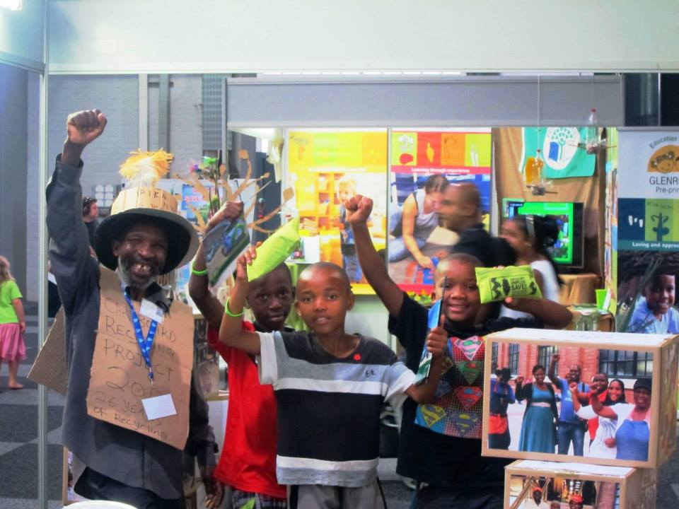 Palmer Street Recycler Leader, Afrika Ntuli with visitors to the Asiye eTafuleni Projects stall with Afrika's signature fist pump honouring informal workers' contributions everywhere. Photo: Tasmi Quazi. Read more here: http://www.aet.org.za/2013/09/promoting-sustainability-inclusion-informal-workers-sle-2013-2/ — at Durban Exhibition Centre.